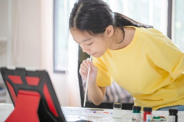 Aziatische kindstudent online leerklasstudie, kind schilderen aan tafel in speelkamer, meisje leert creatieve cursus kunst online tekenen thuis