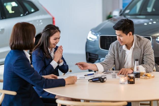 Aziatische klant die de creditcard geeft aan vertegenwoordiger voor aankoop nieuwe auto