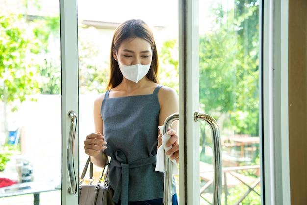 Aziatische klant die papieren zakdoekje gebruikt om de deur te openen. hygiënebescherming corona-virus vóór binnenkomst in restaurant. thaise vrouw met masker wees voorzichtig voordat ze de kamer binnengaat.