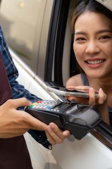 Aziatische klant maakt contactloos mobiel betalen drive thru