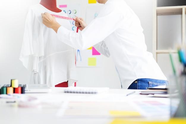 Aziatische kleermaker past kledingstuk ontwerp op mannequin in werkplaats een beetje aanpassing aan haar werk op model in de studio.