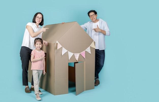 Aziatische klein kind meisje met vader en moeder met haar kartonnen huis geïsoleerd op blauwe lange banner met kopie ruimte voor uw tekst, nieuw huis met familie concept