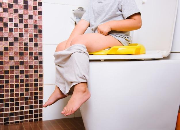 Aziatische klein kind zittend op een accessoire toilet van de kind badkamer