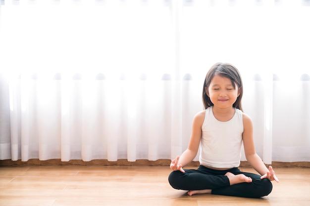 Aziatische klein schattig meisje doet een yoga thuis met ruimte voor tekst toevoegen