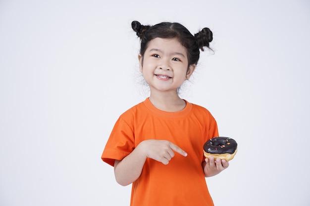 Aziatische klein schattig meisje grote donut eten