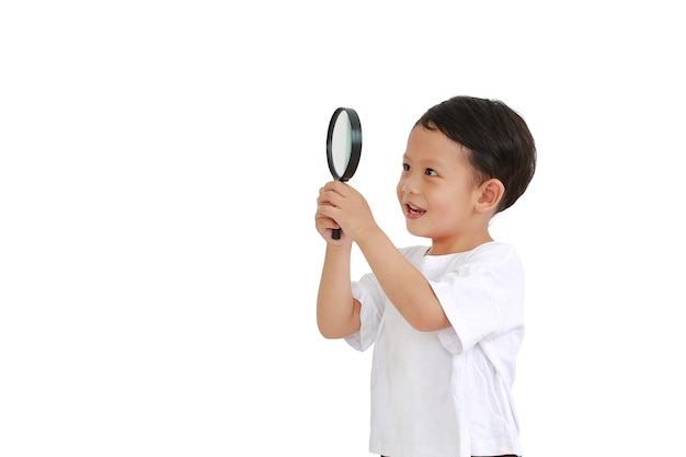 Aziatische kleine babyjongen die door een vergrootglas kijkt naar naast geïsoleerd op een witte achtergrond