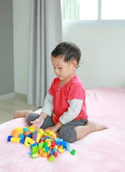 Aziatische kleine babyjongen die kleurrijke plastic blokken speelt met zitten waarin w-sitting wordt genoemd. een kind dat in een slechte houding zit, kan een heupluxatie veroorzaken.