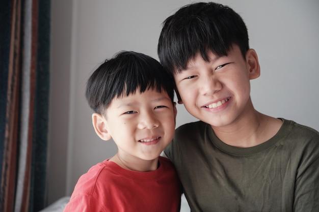 Aziatische kleine broertje en grote broer thuis, gelukkige kinderen portret