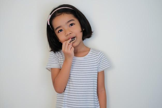 Aziatische kleine jongen die chocoladekoekjes eet, geïsoleerde witte achtergrond