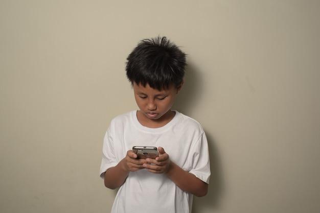 Aziatische kleine jongen die smartphone gebruikt en met een zelfverzekerde uitdrukking naar het scherm van de telefoon kijkt