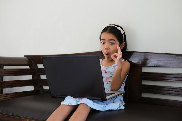 Aziatische kleine jongen die wow-gezichtsuitdrukking laat zien en een ok-vingerteken geeft terwijl hij naar een laptop kijkt