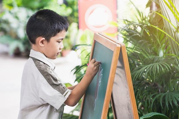 Aziatische kleine jongen punten hand schrijven op blackboard