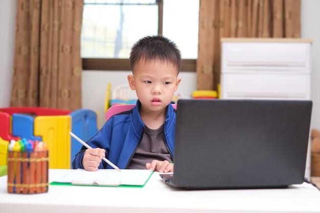 Aziatische kleine jongen tekenen en met behulp van laptop computer huiswerk studeren tijdens zijn online les thuis