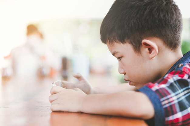 Aziatische kleine jongenszitting die online spel met een slimme telefoon speelt