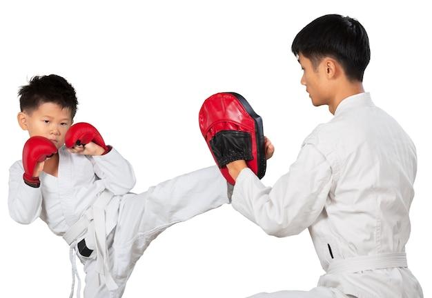 Aziatische kleine karatejongen en verborg leraar in witte kimono