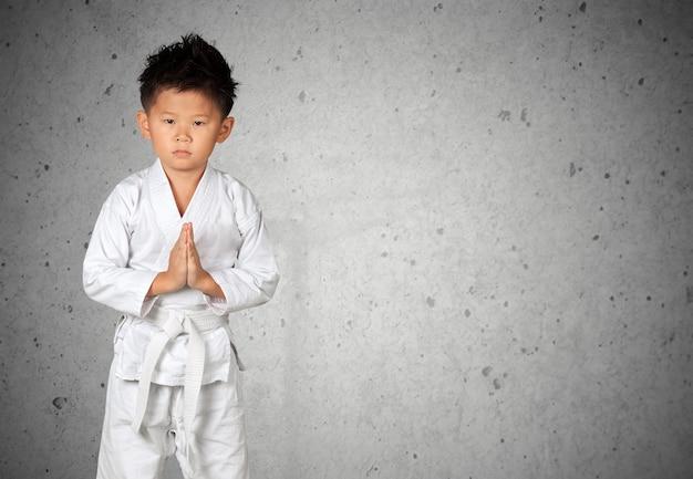 Aziatische kleine karatejongen in witte kimono op achtergrond