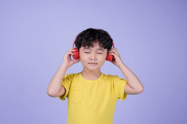 Aziatische kleine knappe schattige jongen met hoofdtelefoon luisteren naar muziek