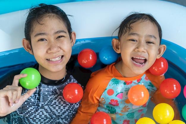 Aziatische kleine meisjes die in een pool spelen