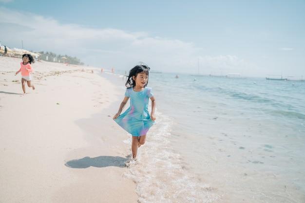 Aziatische kleine meisjes rennen en lachen op het strand