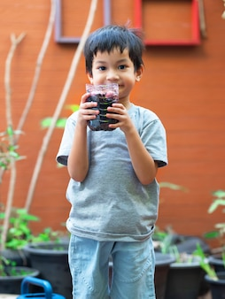 Aziatische kleuterjongen plant sjalot in recycleflescreatieve activiteiten thuis voor kideco life