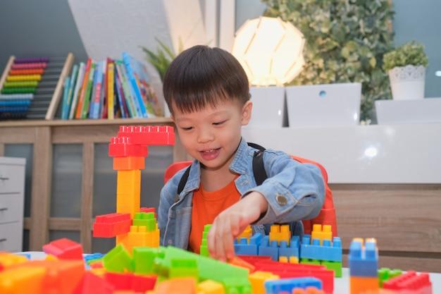 Aziatische kleuterjongen speelblokken met kleurrijke plastic blokken thuis binnen, educatief speelgoed voor jonge kinderen, blijf thuis blijf veilig heb plezier concept
