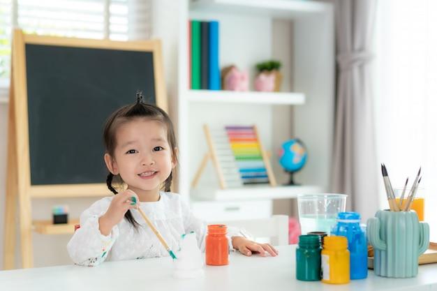 Aziatische kleuterschool meisje en glimlach tijdens het schilderen gips pop met acryl aquarel verf in de woonkamer thuis. thuisonderwijs en afstandsonderwijs.