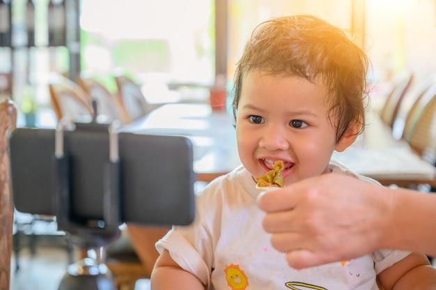 Aziatische kleuterschool met slimme telefoon. kid kijken en leren online op mobiele telefoon. baby nieuwe normale levensstijl.
