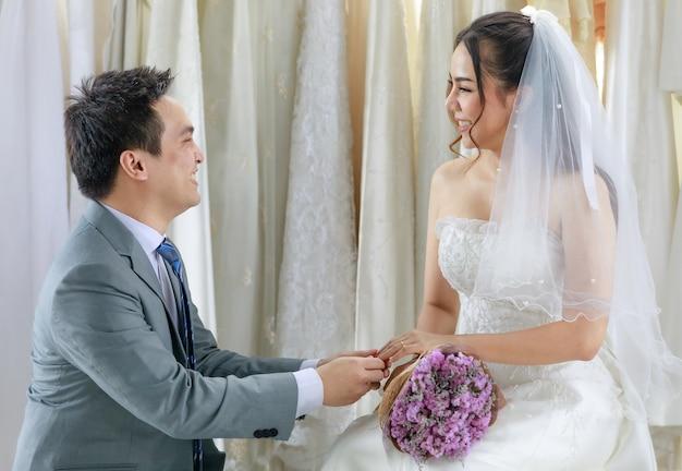 Aziatische knappe bruidegom in grijs formeel pak geknield met rode doos met diamanten ring die jonge mooie gelukkige bruid in witte trouwjurk met haarsluier met bloemboeket in kleedkamer voorstelt.