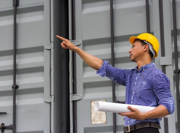Aziatische knappe ingenieursmens die document het plan van het blauwdrukproject dichtbij container bij bouwwerf bekijken. buiten werken om de voortgang van een nieuwbouwproject te zien.