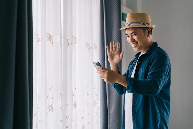 Aziatische knappe man die ochtend in het huis doorbrengt en gelukkig videochat via de smar-telefoon bij het raam.
