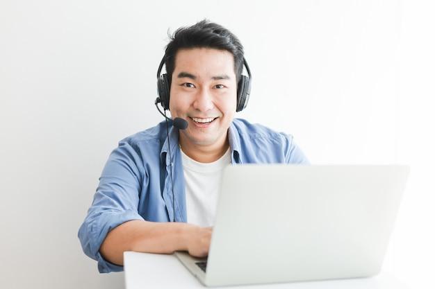 Aziatische knappe man in blauw shirt met behulp van laptop met hoofdtelefoon praten glimlach en blij gezicht