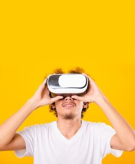 Aziatische knappe man met krullend haar hij met behulp van virtual reality headset of vr-glas