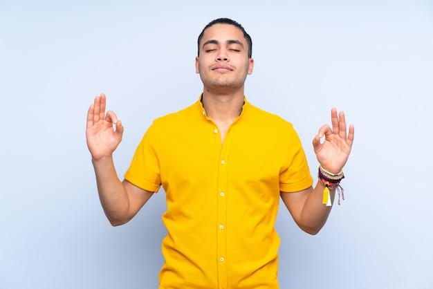 Aziatische knappe man over geïsoleerde achtergrond in zen pose