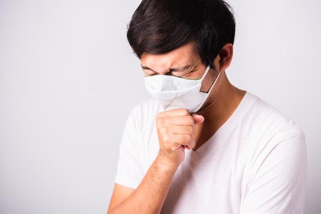 Aziatische knappe mens die beschermend gezichtsmasker draagt tegen coronavirus hij niest hand dichte mond