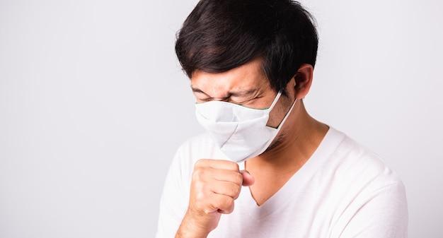 Aziatische knappe mens die het beschermende masker van het doekgezicht dragen tegen coronavirus hij niest hand dichte mond