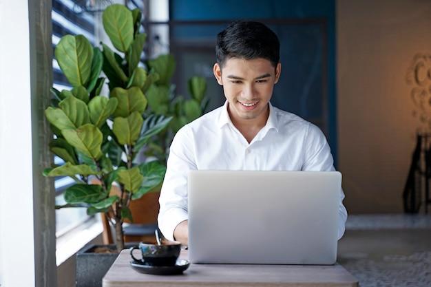 Aziatische knappe zakenman of beambte die bij coffeeshop werken