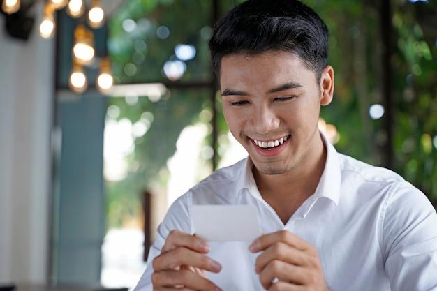 Aziatische knappe zakenman of beambte of jonge student die krediet of debetbetaling gebruikt