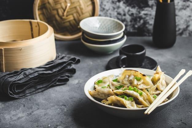 Aziatische knoedels in kom met eetstokjes en bamboestoomboot
