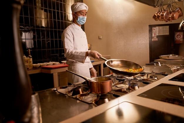 Aziatische kok die een hete pan met groenteplakken kantelt