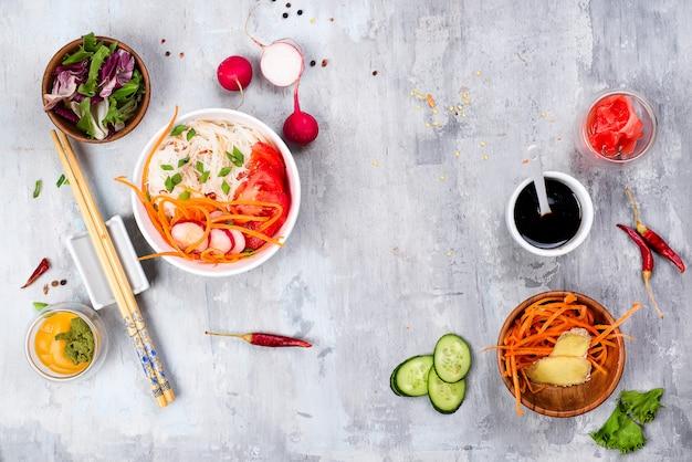 Aziatische kruidige salade van glasnoedels of funchoza met wortelen en groentensalade op steenachtergrond