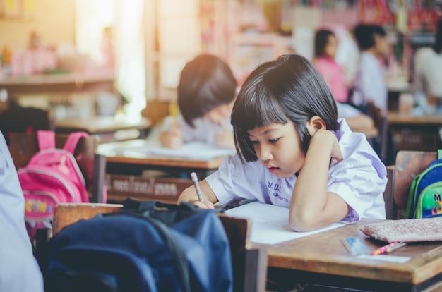 Aziatische landelijke studenten die bij bureaus in de school van thailand werken