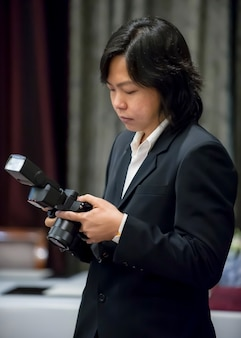 Aziatische langharige fotograaf in marinepak geconcentreerd met zijn camera.