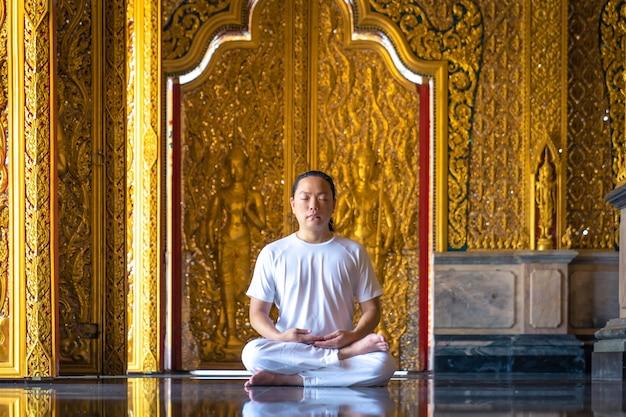 Aziatische langharige man ontspant meditatie met een geheel wit kostuum voor buddist's gouden behang in de tempel, thailand.