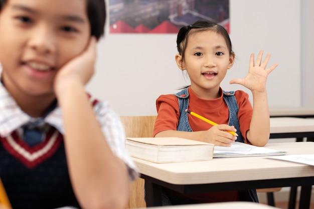Aziatische leerlingen in klaslokaal zitten en meisje die hand opzetten om te antwoorden