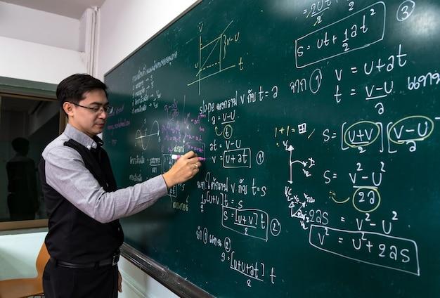 Aziatische leraar die de natuurkunde formular in thaise taal op zwarte raad schrijft