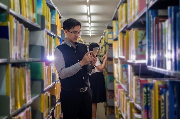 Aziatische leraar die gebruikend slimme mobiele telefoon bevindt zich en het boek kiest voor het geven van les