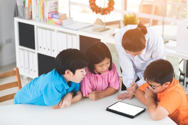 Aziatische leraar en kinderen vermaken zichzelf met behulp van digitale tablet