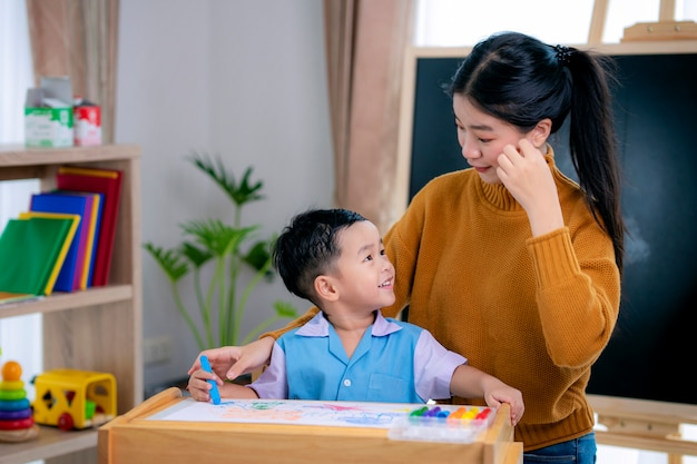 Aziatische leraar in de klas op de kleuterschool leert haar student tekenen