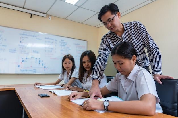 Aziatische leraar les geven aan groep van studenten in de klas