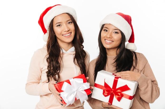 Aziatische leuke dameszusters die de hoeden van kerstmissanta dragen